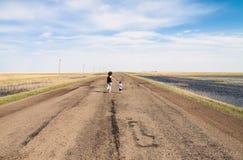 Mère et enfant courant sur la route vide Images libres de droits