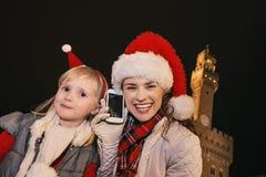 Mère et enfant dans des chapeaux de Noël parlant du téléphone portable Photographie stock libre de droits