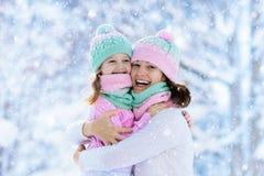 Mère et enfant dans des chapeaux tricotés d'hiver dans la neige photo libre de droits