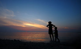 Mère et enfant dans le coucher du soleil Photos stock