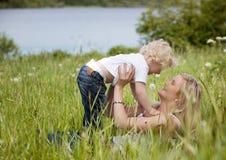 Mère et enfant dans le pré Photographie stock libre de droits