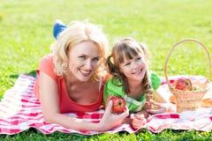 Mère et enfant de famille ayant le pique-nique dans le parc d'été Image stock