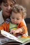 Mère et enfant en bas âge avec le menu Photos stock
