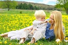 Mère et enfant en bas âge détendant dans le pré de fleur Photos libres de droits
