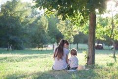 Mère et enfant en bas âge s'asseyant sous l'arbre Photo stock