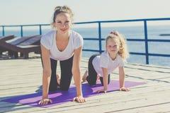 Mère et enfant faisant des sports dehors Photographie stock