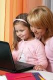 Mère et enfant heureux avec l'ordinateur portatif Photo stock