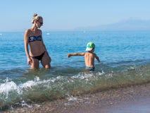 Mère et enfant jouant à la plage tropicale Vacances d'été de mer de famille Jeu de garçon de maman et d'enfant et construire le c images stock