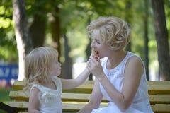 Mère et enfant mangeant la crème glacée pendant l'été dehors Images stock