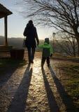 Mère et enfant marchant dans la lumière de coucher du soleil Images libres de droits