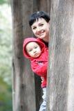 Mère et enfant regardant à l'extérieur de l'arbre Photographie stock