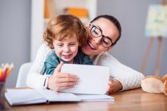 Mère et enfant regardant le comprimé Images stock