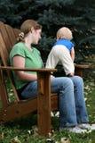 Mère et enfant s'asseyant à l'extérieur Photographie stock libre de droits
