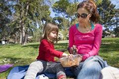 Mère et enfant s'asseyant en parc partageant des pâtes Photos libres de droits