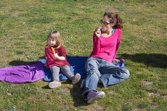 Mère et enfant s'asseyant mangeant des esquimaux en parc Image stock