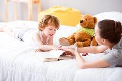 Mère et enfant se trouvant sur le lit Image stock