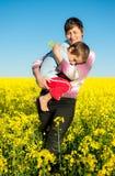 Mère et enfant sur un gisement de graine de colza Photographie stock