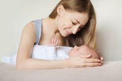 Mère et enfant sur un lit blanc Photo libre de droits
