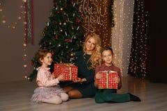 Mère et enfants échangeant et ouvrant des cadeaux de Noël Image stock