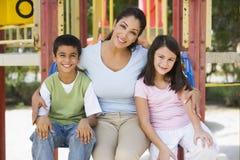 Mère et enfants dans la cour de jeu Photo stock