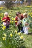 Mère et enfants dans le domaine de jonquille Image stock