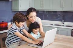 Mère et enfants de sourire travaillant sur l'ordinateur portable photographie stock