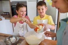 Mère et enfants faisant ensemble la tarte aux pommes dans la cuisine à la maison Enfants aidant la mère Photographie stock libre de droits