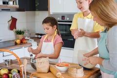 Mère et enfants faisant ensemble la tarte aux pommes dans la cuisine à la maison Enfants aidant la mère Image stock