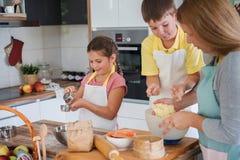 Mère et enfants faisant ensemble la tarte aux pommes dans la cuisine à la maison Enfants aidant la mère Photos stock