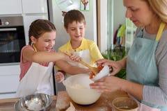 Mère et enfants faisant ensemble la tarte aux pommes dans la cuisine à la maison Enfants aidant la mère Images libres de droits