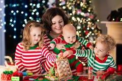 Mère et enfants faisant la maison de pain de gingembre sur Noël Images stock