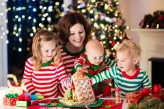 Mère et enfants faisant la maison de pain de gingembre sur Noël Photos libres de droits