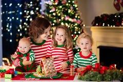 Mère et enfants faisant la maison de pain de gingembre sur Noël Image libre de droits