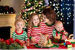 Mère et enfants faisant la maison de pain de gingembre sur Noël Photo stock