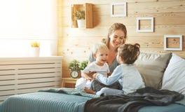 Mère et enfants heureux de famille dans le lit Photos stock