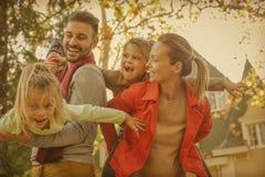 Mère et enfants et jeu de transport de père avec eux Images stock