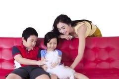 Mère et enfants jouant avec le chien Images stock