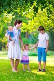 Mère et enfants jouant en parc Photos stock