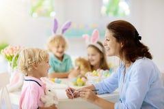 Mère et enfants, oeufs de pâques de coloration de famille photographie stock