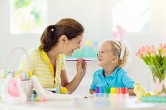 Mère et enfants, oeufs de pâques de coloration de famille images stock
