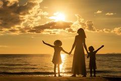Mère et enfants se tenant sur la plage au temps de coucher du soleil Photos libres de droits