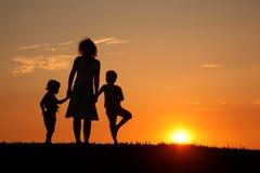 Mère et enfants sur la silhouette de coucher du soleil Photographie stock