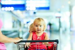 Mère et enfants sur le chariot de bagage dans l'aéroport Photographie stock libre de droits