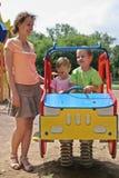 Mère et enfants sur le jouet de véhicule Photographie stock