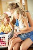 Mère et enfants triant la blanchisserie photographie stock