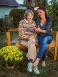 Mère et fille à l'aide d'un téléphone portable dans le jardin Photo libre de droits