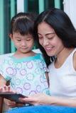Mère et fille à l'aide de la Tablette de Digital Famille passant le temps t Photographie stock