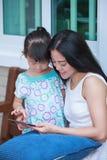 Mère et fille à l'aide de la Tablette de Digital Famille passant le temps t Photo libre de droits