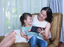 Mère et fille à l'aide de la Tablette de Digital Famille passant le temps t Image libre de droits