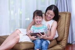 Mère et fille à l'aide de la Tablette de Digital Famille passant le temps t Photos stock